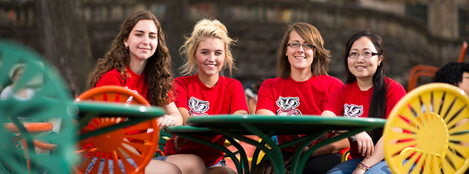 Great People Scholars, from left, Alyssa Sage, Asimina Pappas, Tressa Franzmeier and MaipaThao, sport their Wisconsin Alumni Association Red Shirts on the Memorial Union Terrace. Proceeds from sales of the Red Shirt go directly to Great People Scholarships.